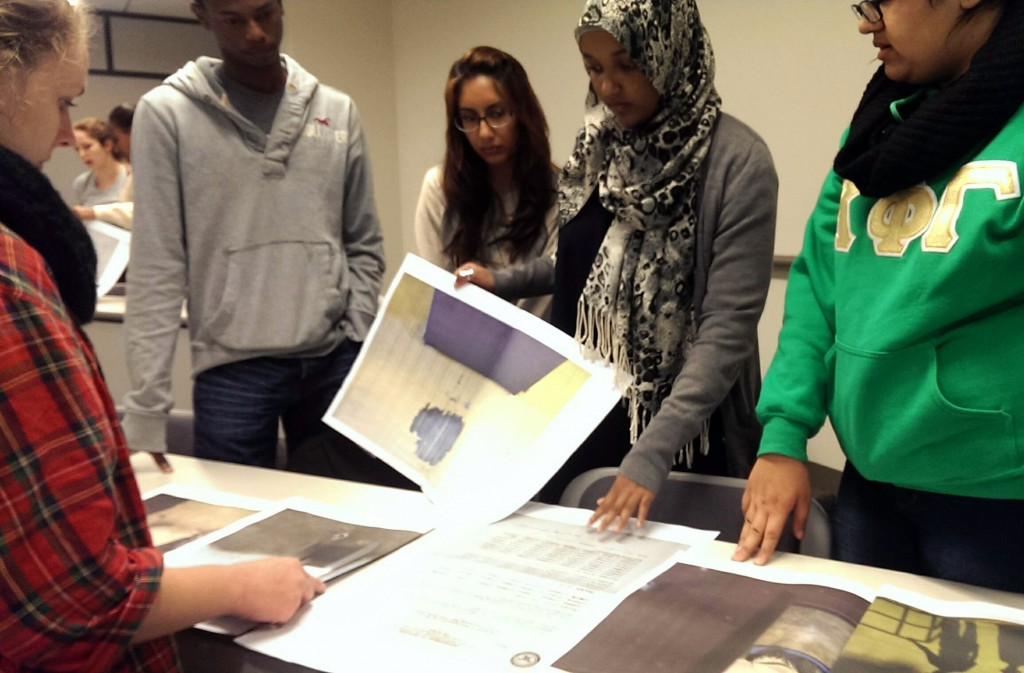 Mason Arlington Fellows prepare to present their edit of guest lecturer and photojournalist Louie Palu's Guantanamo Bay  photos using his independently-published concept newspaper.