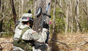 "A cadet, armed with a paintball gun, keeps a look out for ""enemy"" forces."