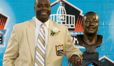 Darrell Green standing next to his bust in the Pro Football Hall of Fame during his induction. (Credit: Kiichiro Sato, AP)