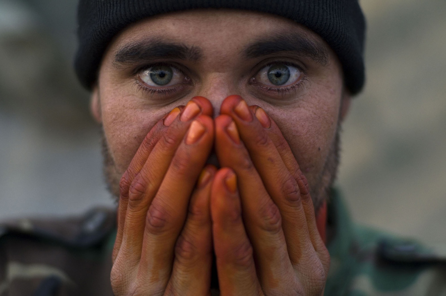 An Afghan soldier seen warming his henna stained hands from EID worship on the front lines in Zhari District, Kandahar, Afghanistan. From the documentary film Kandahar Journals. www.kandaharjorunals.com photo Louie Palu/ZUMA Press ©