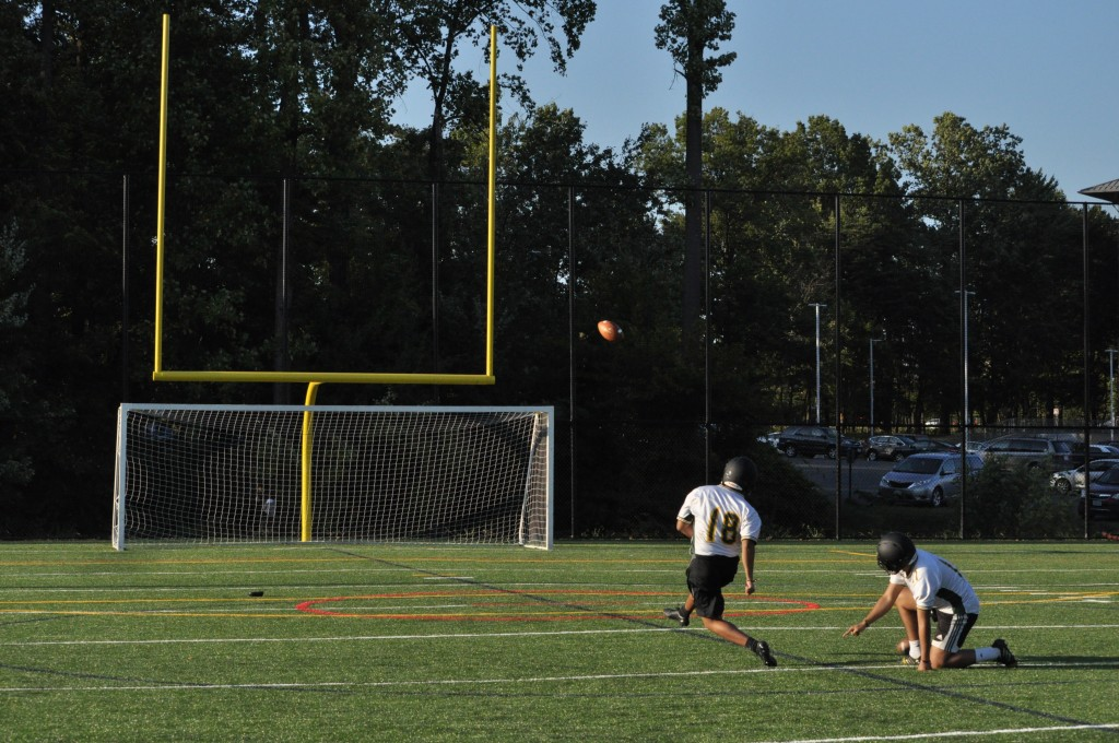 Kicker Ray De La Cruz sends the ball towards the goalposts during practice on September 13. Credit: Dave Schrack, Fourth Estate